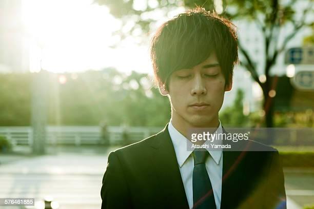 young businessman closing eyes on street - 目を閉じた ストックフォトと画像