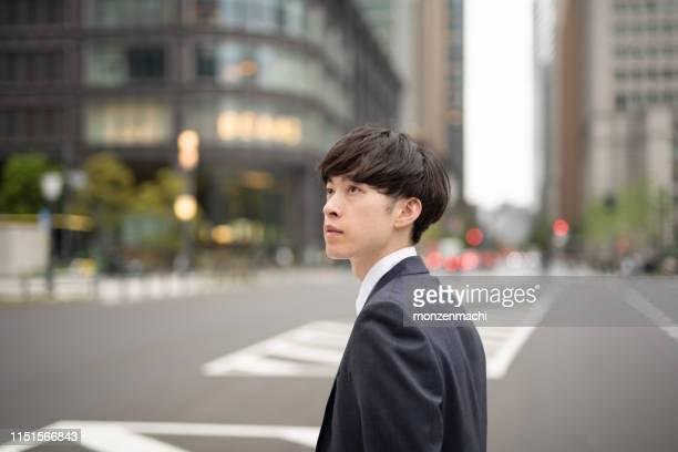 若いビジネスマンが通勤し、通りを歩いている - one young man only ストックフォトと画像