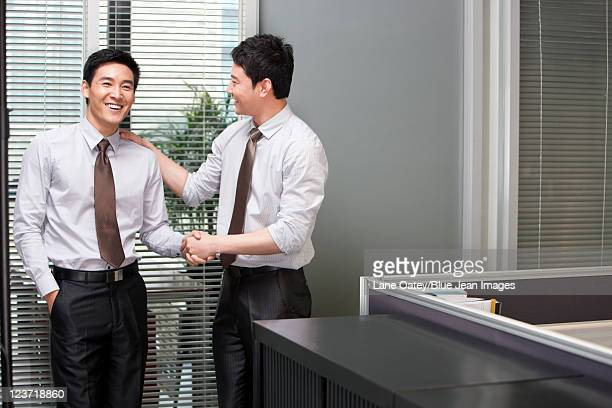 Young Businessman Congratulating Other Young Businessman