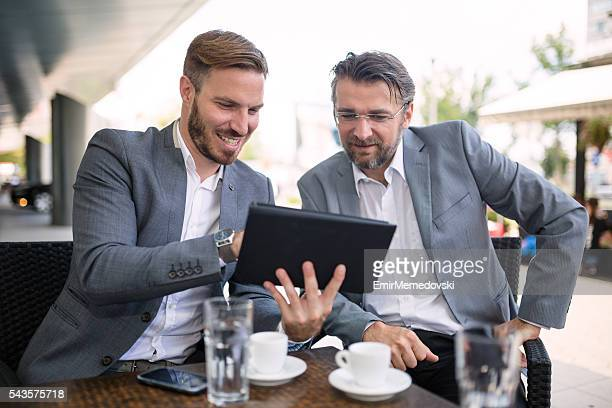 Young businessman cooperating with senior colleague outdoors.