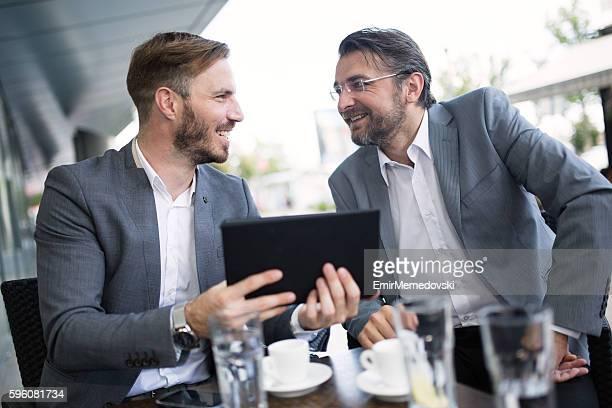Junge Geschäftsmann Zusammenarbeit mit senior Kollegen im Freien.