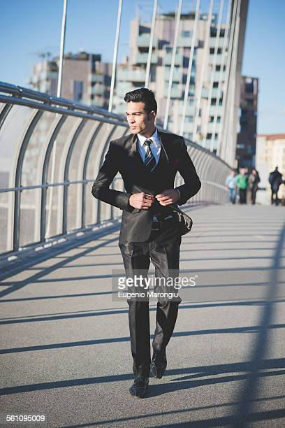 Young businessman crossing bridge