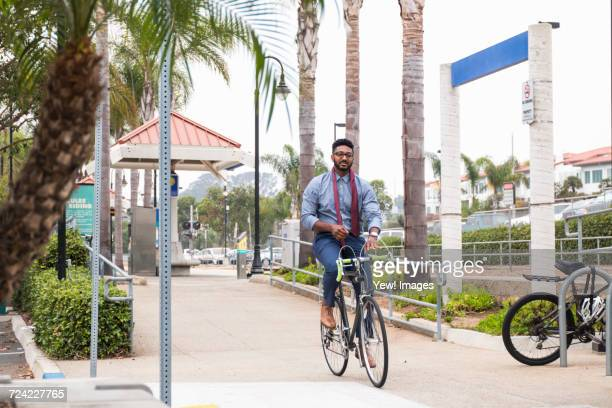 Young businessman cycling hands free on rail station platform
