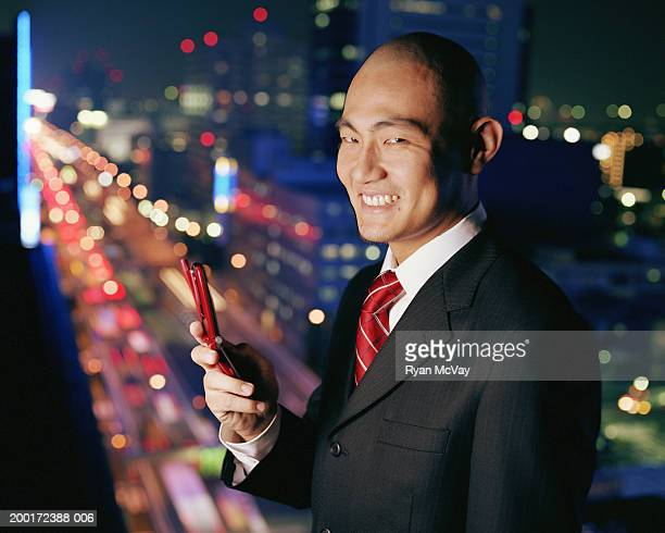 Young businessman dialing cell phone, urban scene in background, night
