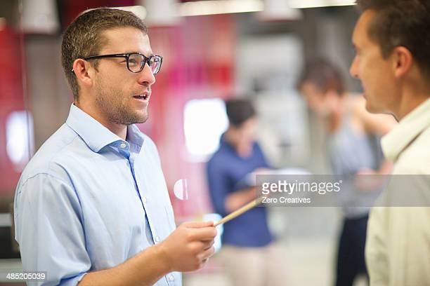 Young businessman discussing ideas with colleague