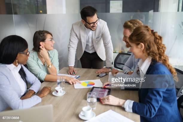 同僚と販売分析を議論する青年実業家