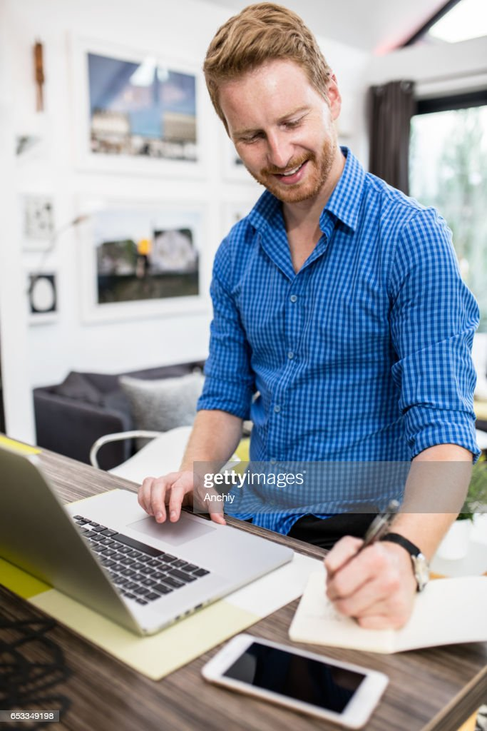 Young businessman doing online research, taking notes. : Stock Photo