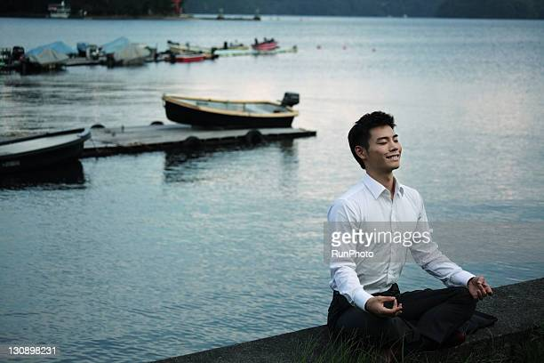 young businessman doing yoga in the lake