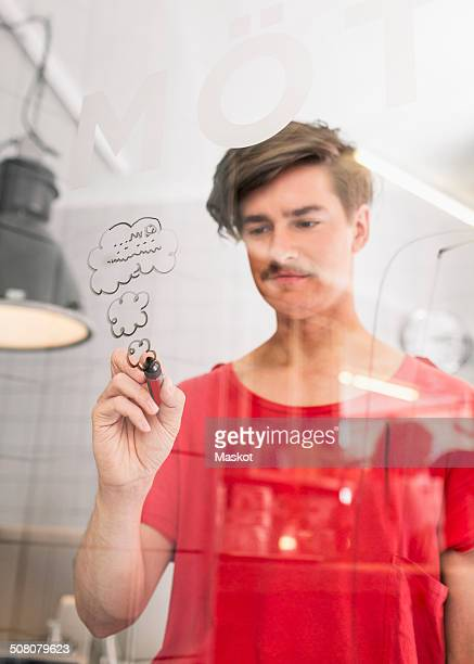 Young businessman drawing clouds on transparent glass in creative office