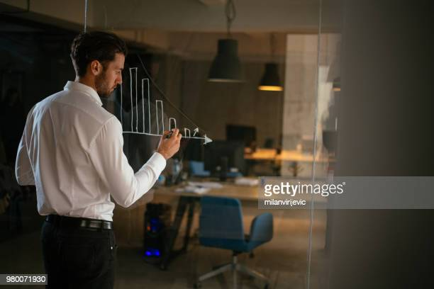 Young businessman drawing graph on glass wall