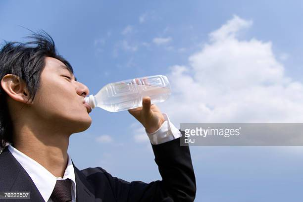Young businessman drinking a bottle of water under the blue sky, side view, Japan