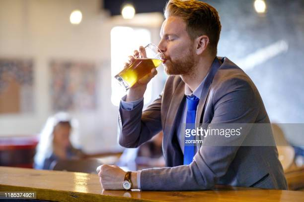young businessman drinking beer at the bar counter - ale stock pictures, royalty-free photos & images