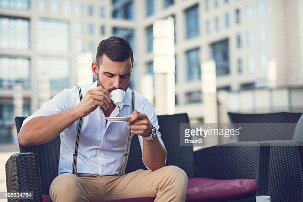 Young businessman drinking espresso coffee in a cafe.