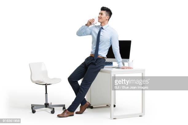 young businessman drinking milk in office - shirt and tie stock pictures, royalty-free photos & images