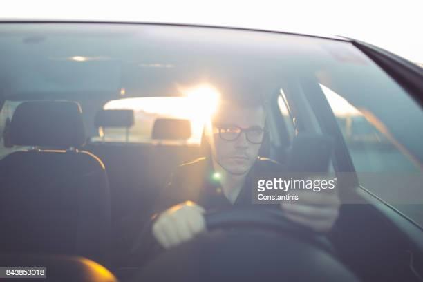 車を運転して、スマート フォンを使用して青年実業家