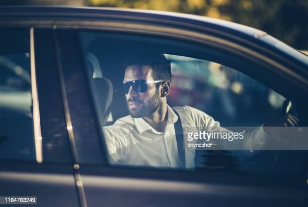 jonge zakenman die een auto in omgekeerde richting rijdt. - terugtrekken stockfoto's en -beelden