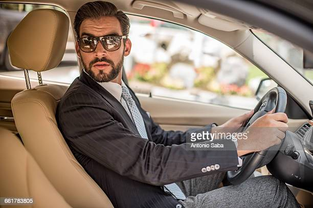 Young businessman driving car looking over his shoulder, Dubai, United Arab Emirates