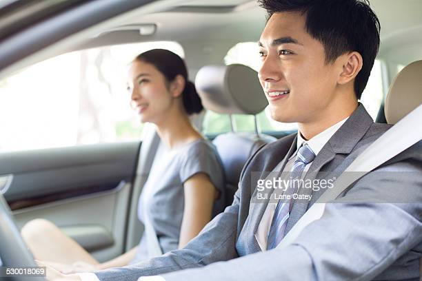 Young businessman driving car with his wife sitting next to him