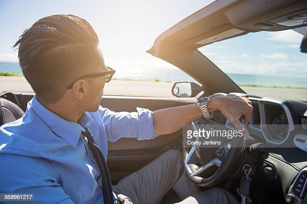 Young businessman driving convertible at coast
