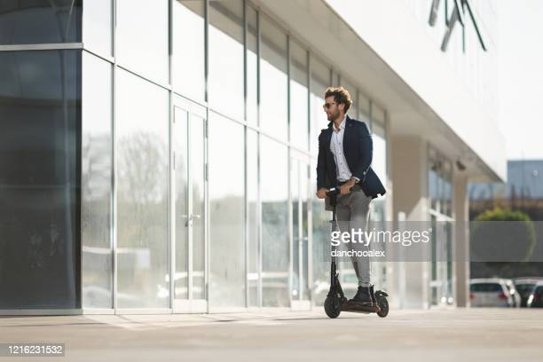 young businessman driving e-scooter in the city - electric scooter stock pictures, royalty-free photos & images