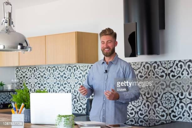 giovane uomo d'affari durante la videochiamata a casa - izusek foto e immagini stock