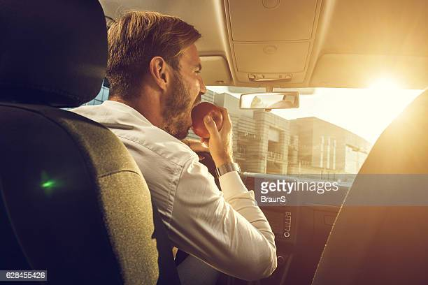Young businessman eating an apple in the car.