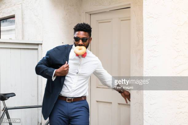 young businessman eating doughnut and closing front door - dringendheid stockfoto's en -beelden