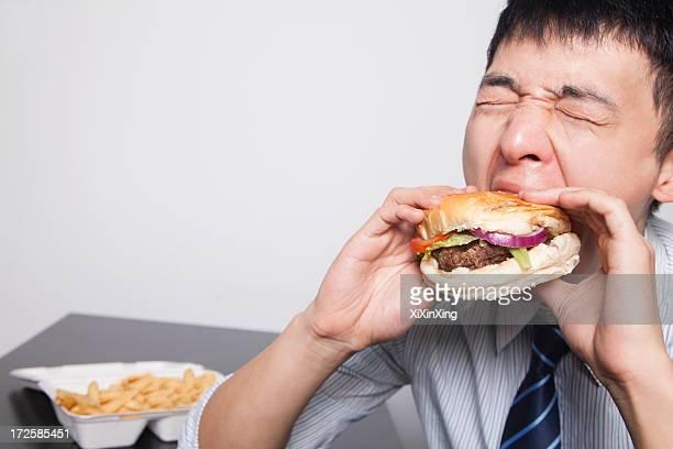 Young businessman enjoying a burger