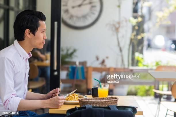 仕事をしながらホテルで朝食を楽しむ青年実業家
