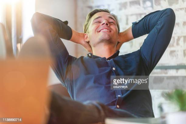 young businessman enjoying his success. - satisfaction stock pictures, royalty-free photos & images