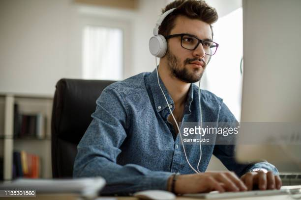 young businessman enjoying music and working on computer - educazione online foto e immagini stock