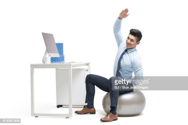 young businessman exercising in office while sitting on fitness ball - shirt and tie stock pictures, royalty-free photos & images