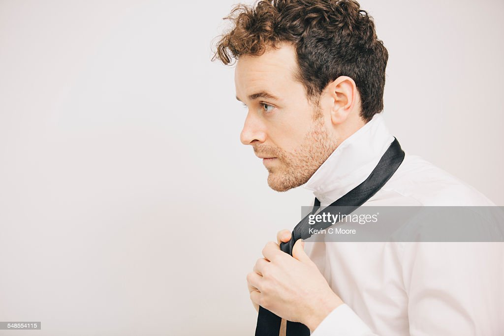 Young businessman fastening tie in apartment bedroom : Stock Photo