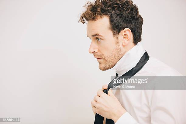 Young businessman fastening tie in apartment bedroom