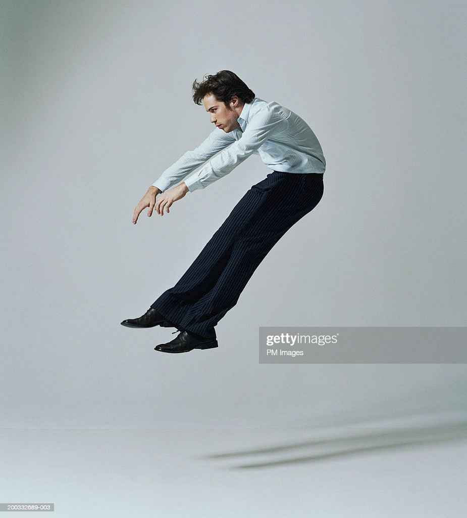 Young businessman flying backwards, side view : Stock Photo