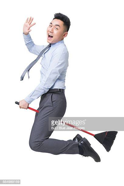 Young businessman flying on broom