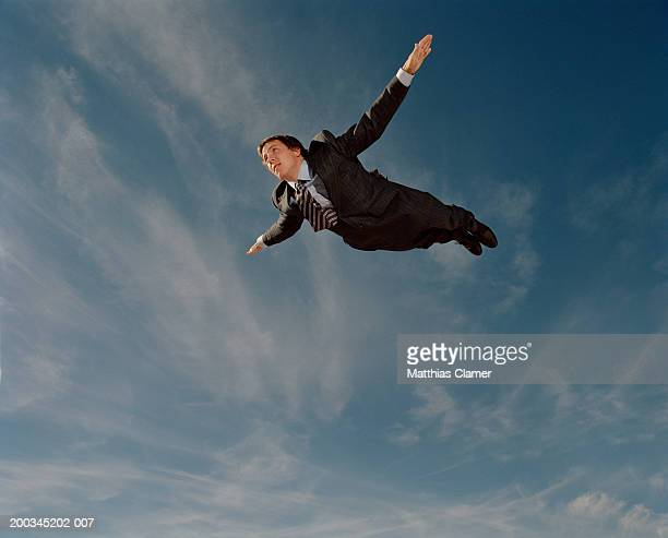 Young businessman flying through sky, side view