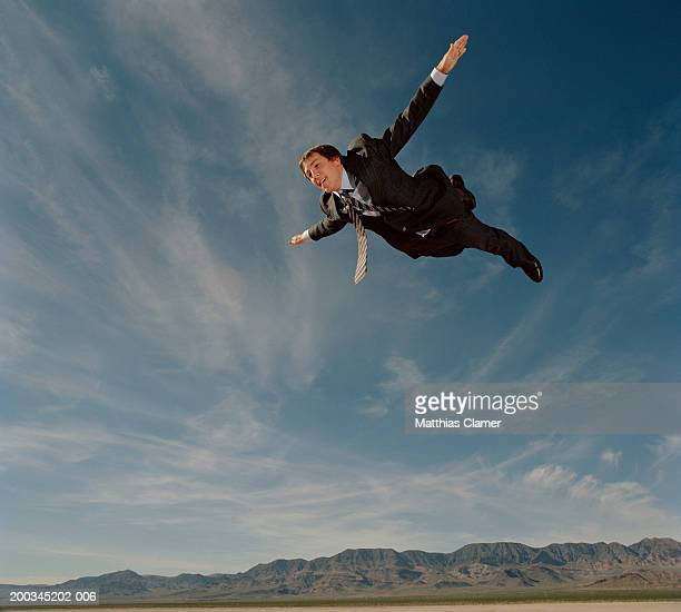 Young businessman flying through sky, smiling, side view