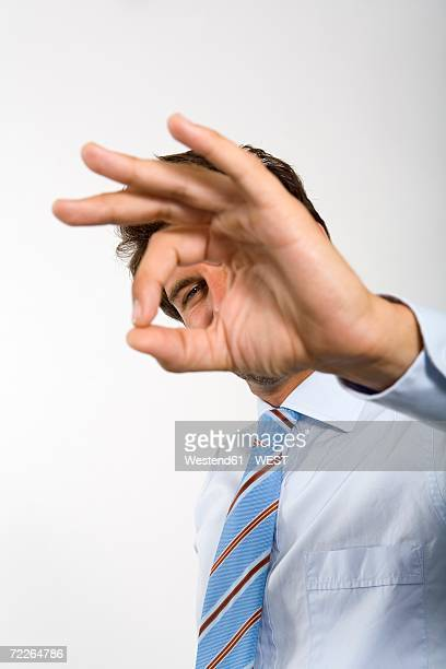 Young businessman gesturing ok sign (focus on background)