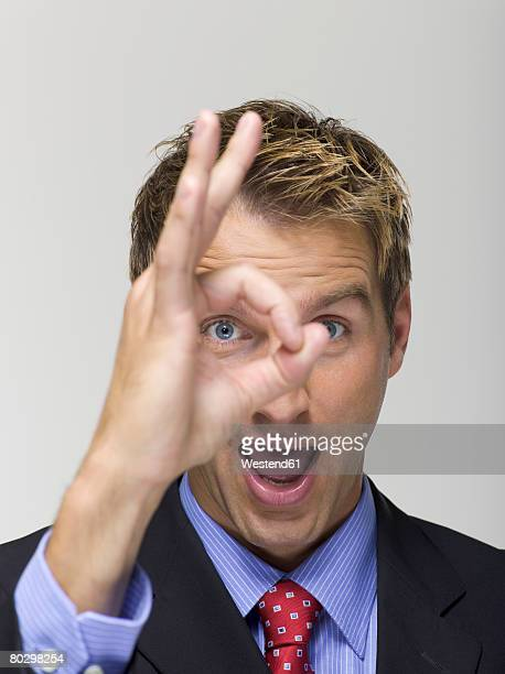 Businessman gesturing ok sign with fingers over eye, portrait, close-up