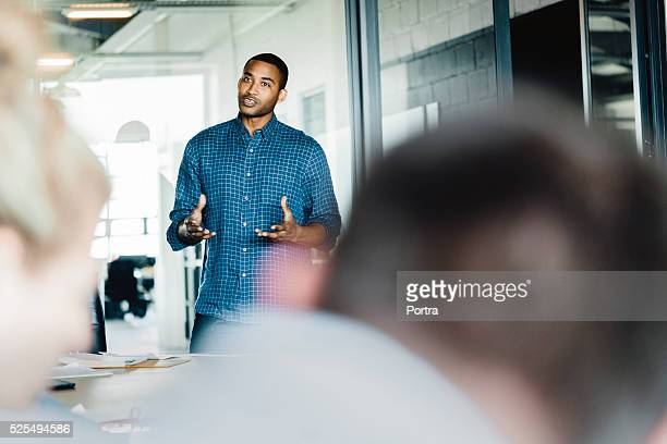 Young businessman giving presentation in office