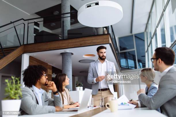 young businessman giving presentation in the office - leading stock pictures, royalty-free photos & images