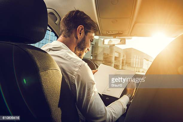 Young businessman going through reports in the car.