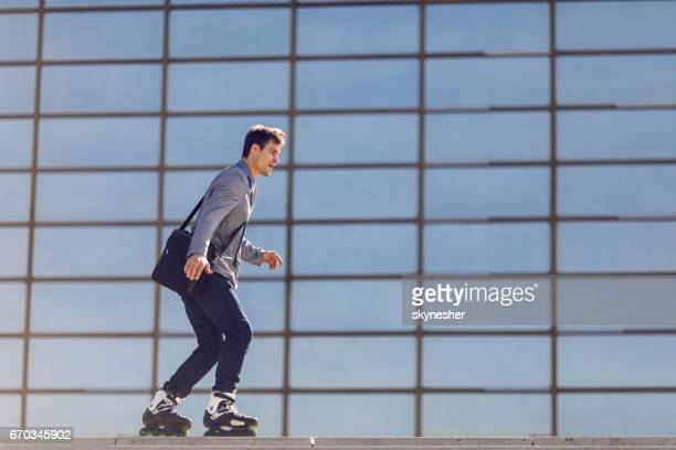 young businessman going to work on roller skates. - inline skate stock photos and pictures