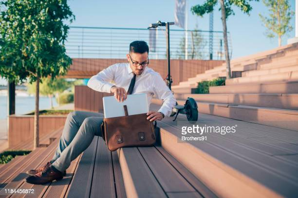 young businessman going trough his briefcase - brown purse stock pictures, royalty-free photos & images