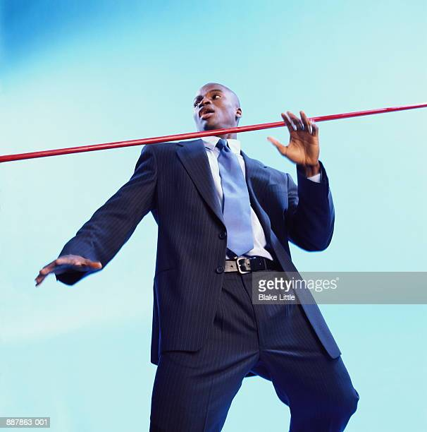 Young businessman going under red limbo bar