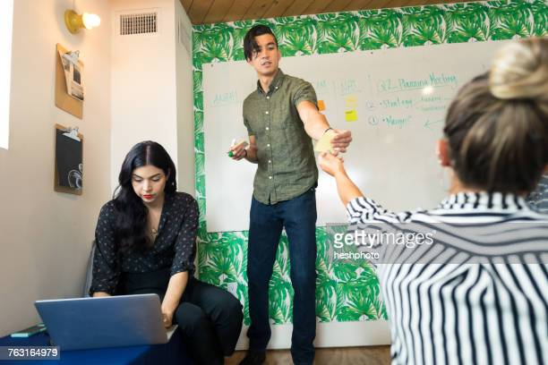 young businessman handing out adhesive notes in creative meeting room - heshphoto stock pictures, royalty-free photos & images