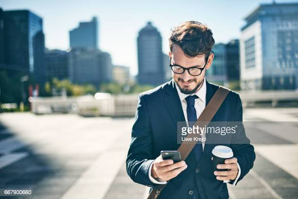 Young businessman having coffee while using smart phone