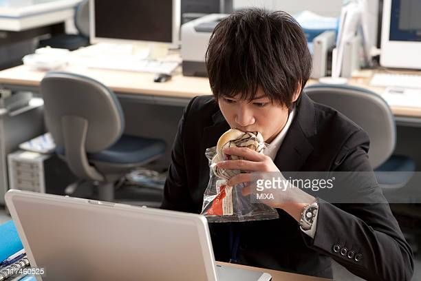 Young businessman having meal at desk