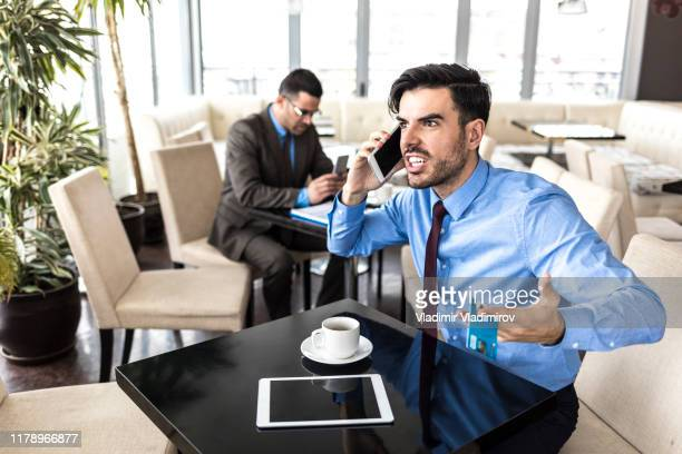 young businessman having problems with credit card - fury stock pictures, royalty-free photos & images